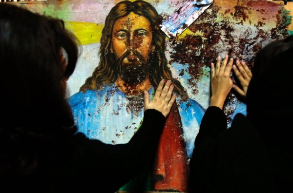 Egyptian Christians touch a blood-splattered image of Jesus Christ, inside the Coptic Orthodox church in Alexandria, January 2, 2011. A bomb killed at least 21 people outside the church early on New Year's Day and the Interior Ministry said a foreign-backed suicide bomber may have been responsible. REUTERS/Amr Abdallah Dalsh (EGYPT - Tags: CIVIL UNREST RELIGION IMAGES OF THE DAY)